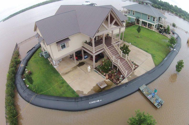 Un gigantesco tubo di plastica nera circonda la casa proteggendola dall'acqua / Aquadam Inc.