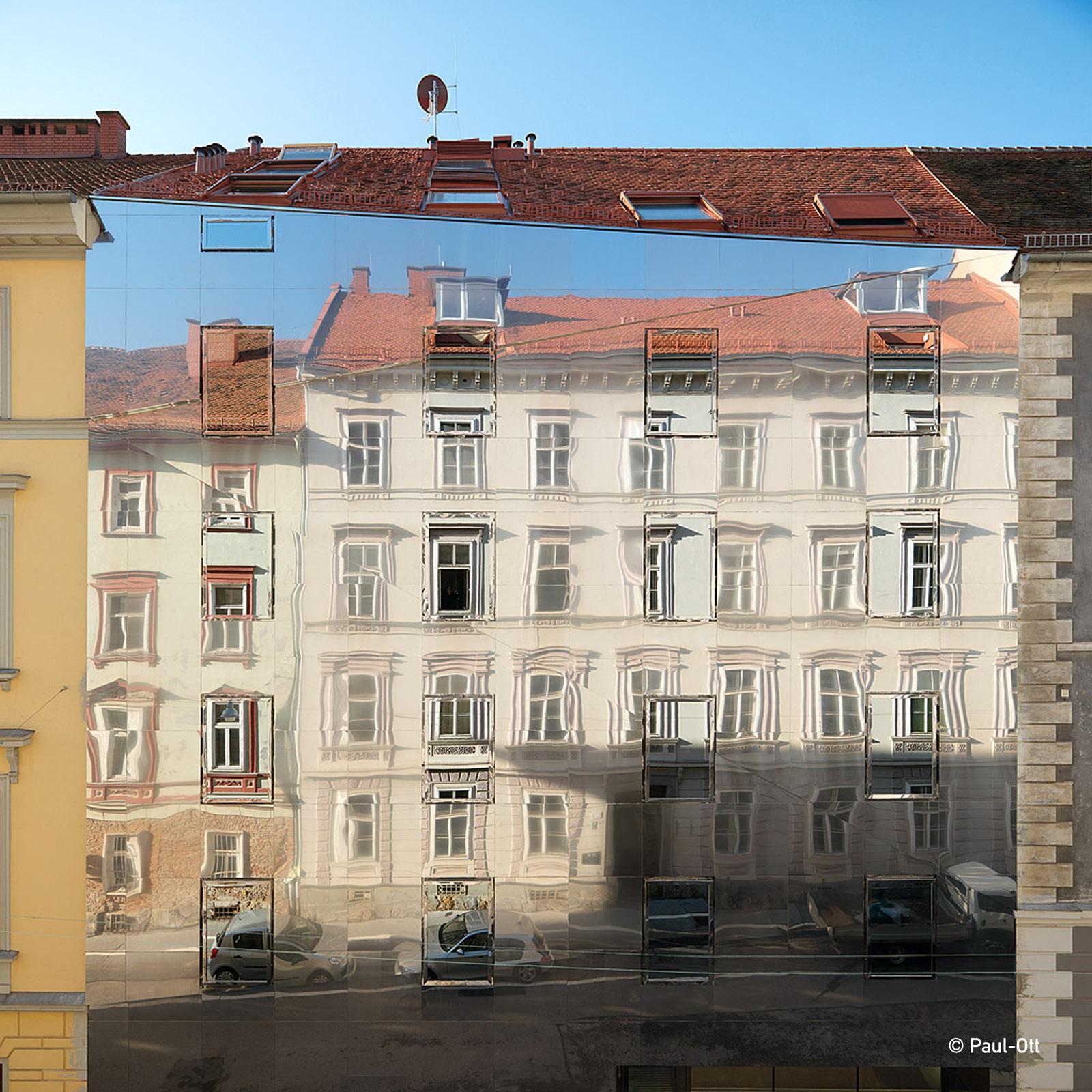 La casa è rivestita di acciaio inossidabile che riflette l'edificio vicino