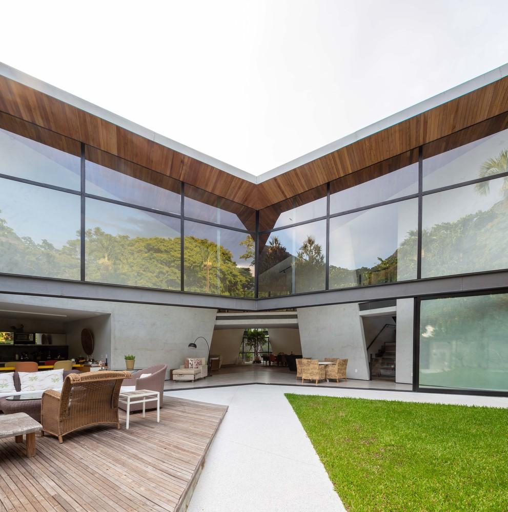 Con grandi finestre che illuminano l'interno / Tiago Tardin via Archdaily